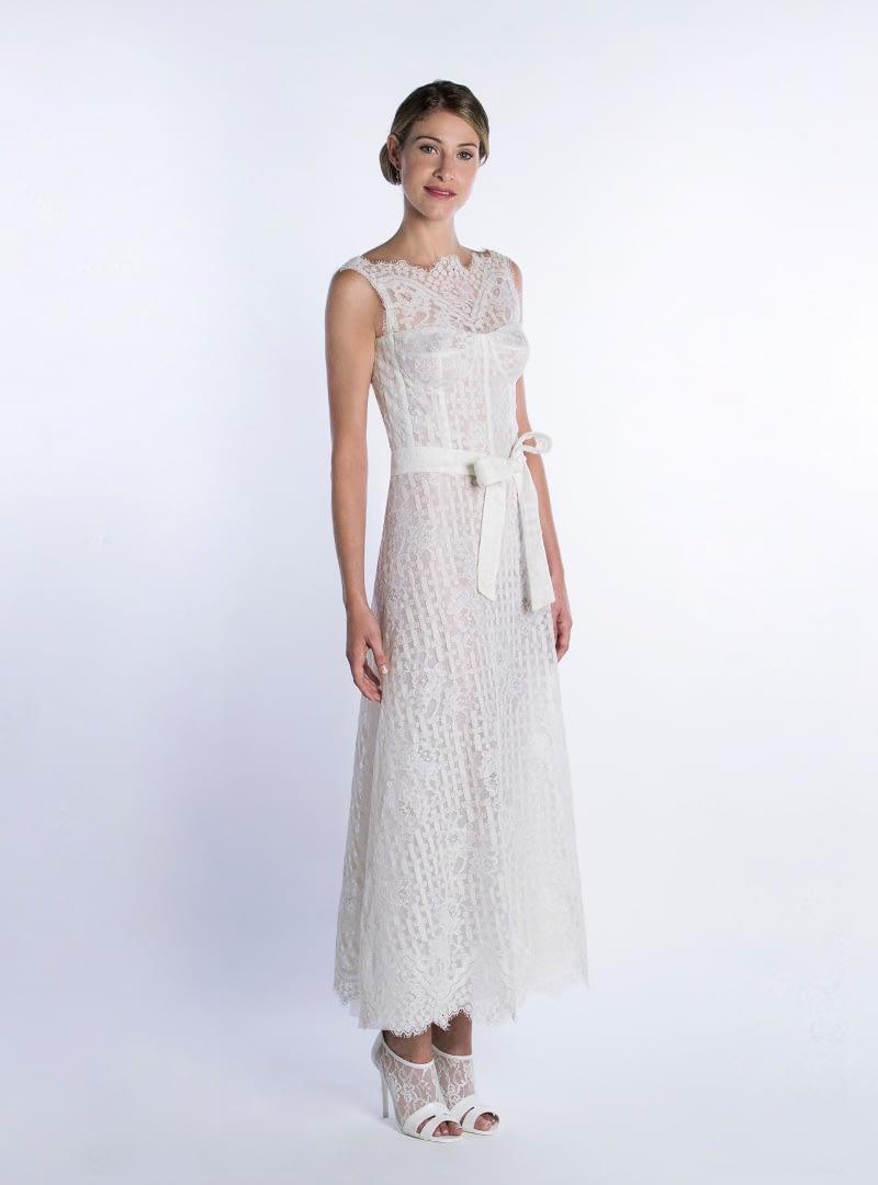 Vestit de núvia curt per noces civils. Disseny d'Alta Costura de CRISTINA SAURA. Precisa cotilleria, defineix el cos, i està construït amb encaix de tema geomètric-floral.