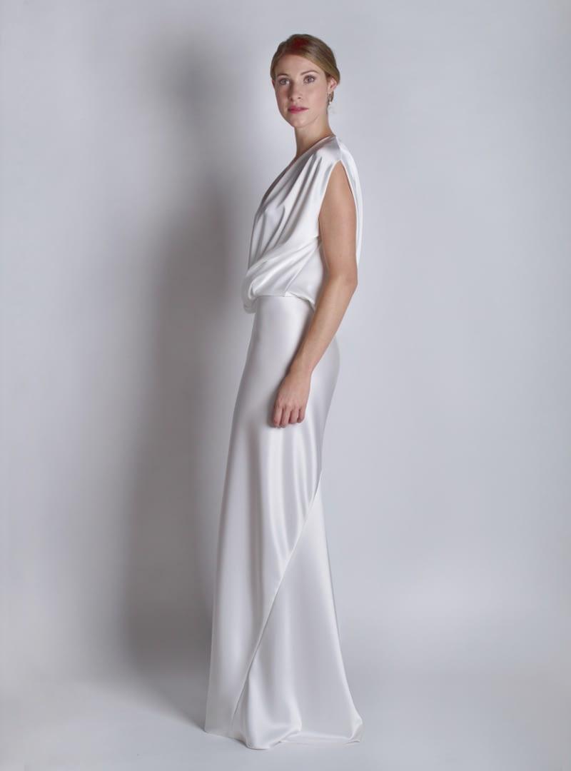Jana és un disseny CRISTINA SAURA per a núvia i festa, de línia columna, en què cobra protagonisme la seva generós escot i sensual caient sobre la línia de maluc.