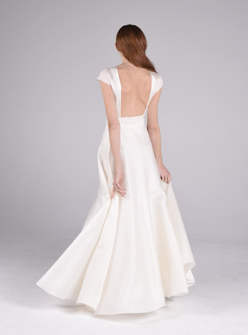 Olivia és un afavoridor disseny per vestit de núvia de CRISTINA SAURA. Construït amb triple organdí de seda, el tall defineix la línia de la cintura fins al maluc i augmenta el seu volum generosament en el baix.