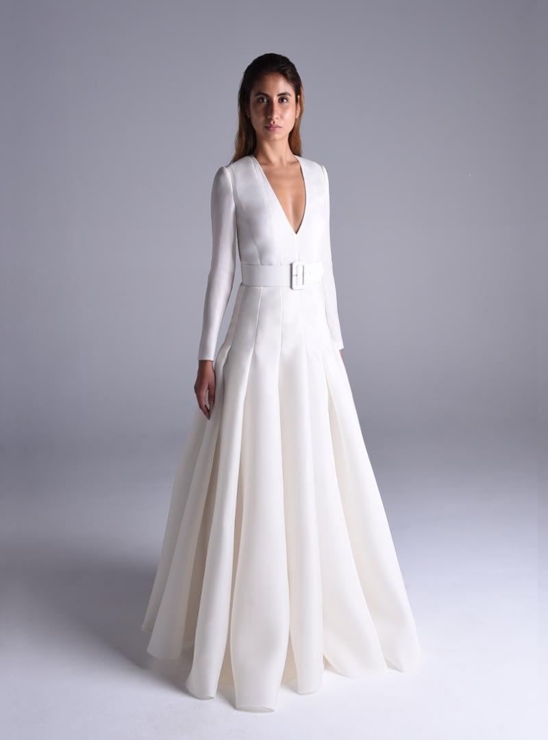 El cuerpo del vestido de Alta Costura, de corte clásico, acompaña el trazado de la falda dando continuidad a cada pliegue con una costura.